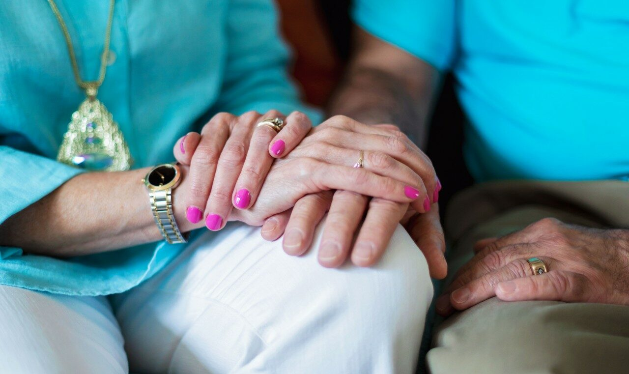 https://thepostage.com/wp-content/uploads/2020/09/Older-Couple-Holding-Hands-Small-e1626469308700.jpg